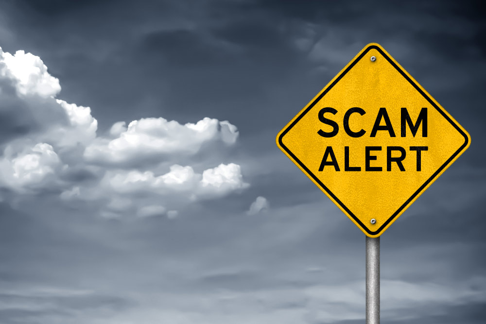 caution road sign stating scam alert